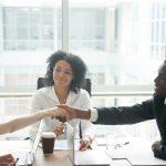 Smiling african businessman handshaking greeting caucasian businesswoman at group meeting