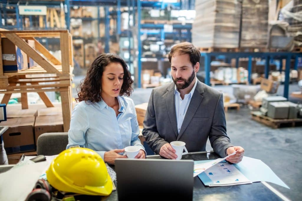Business people checking list and inventory on laptop at warehouse